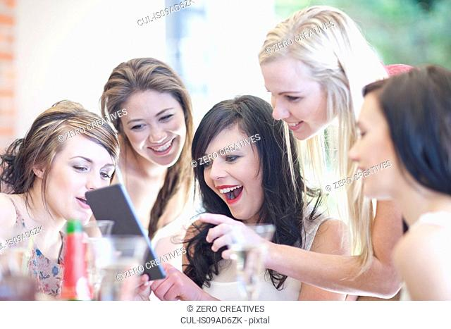 Female friends laughing at digital tablet