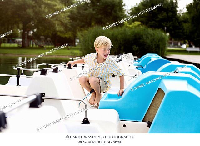 Portrait of smiling little crouching on a paddleboat at a lake