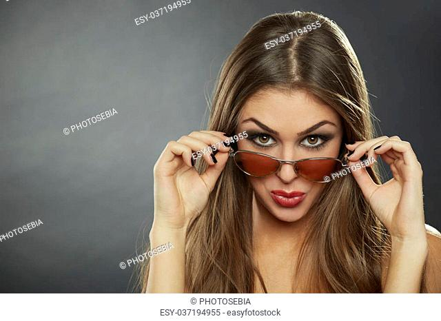 Sexy flirtatious long-haired woman looking over her sunglasses and making a funny surprised face over grey background