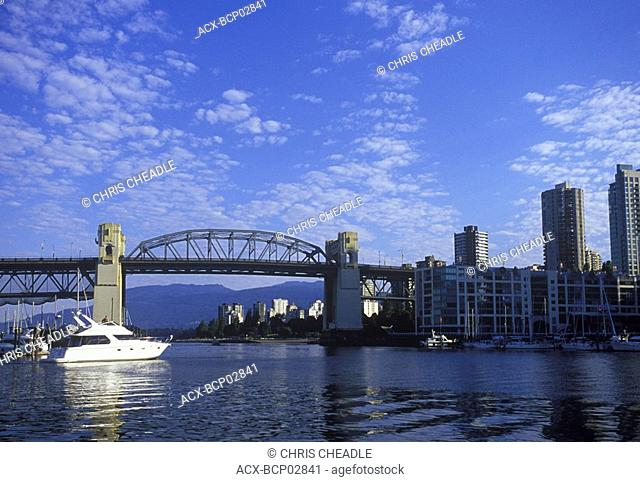 Burrard bridge frames view to West End, with yacht underway, Vancouver, British Columbia, Canada