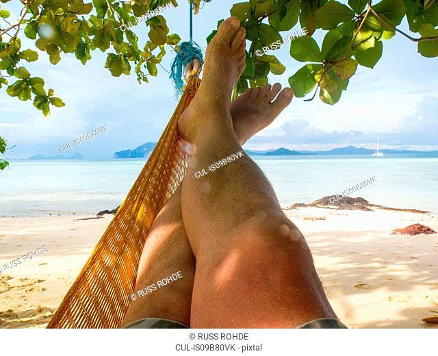 Mans legs in hammock on beach, Koh Kradan, Thailand, Asia