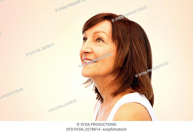 portrait of smiling senior woman over beige