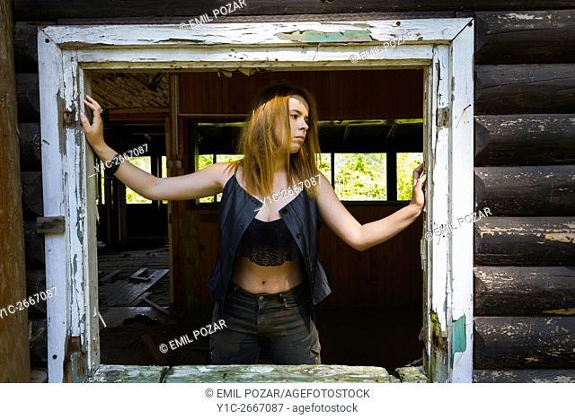 Teen girl framed by rotten window