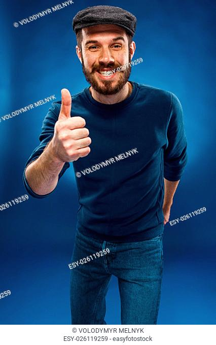The young smiling man in cap showing something and making the ok thumbs up hand sign on blue background