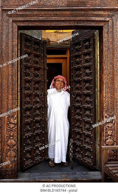 Smiling man opening ornate doors