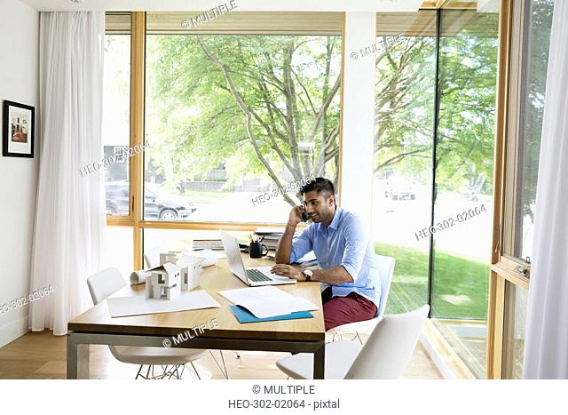 Young man talking on cell phone working at laptop at dining table