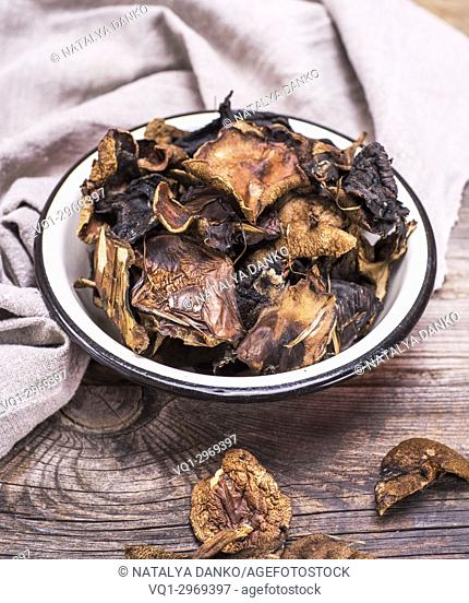 dry forest mushrooms in an iron plate on a gray wooden background