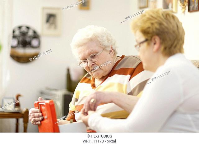 Old woman giving money to geriatric nurse