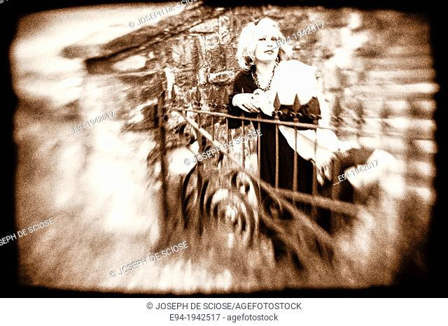 Black & white portrait of a 34 year old blond woman looking at the camera standing by an iron fence