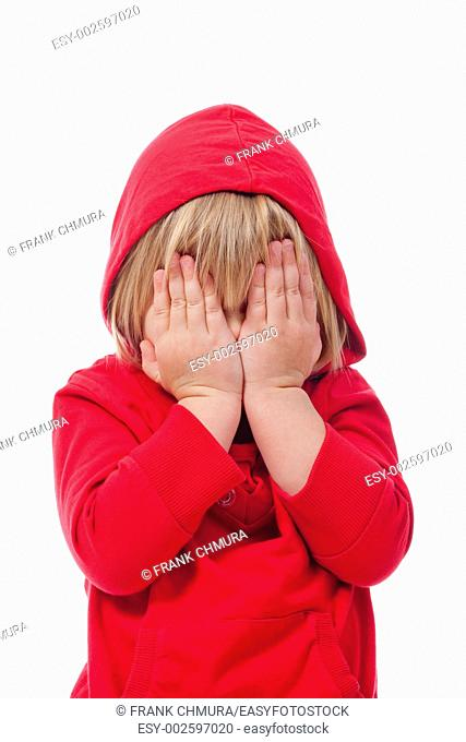 little girl with blond hair covering her face with hands - isolated on white