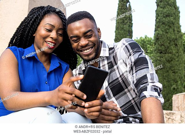 Portrait of smiling young couple looking at cell phone