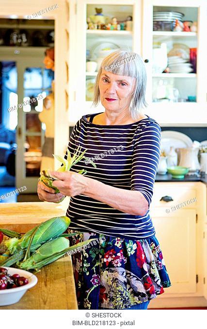 Older Caucasian woman shucking corn in kitchen