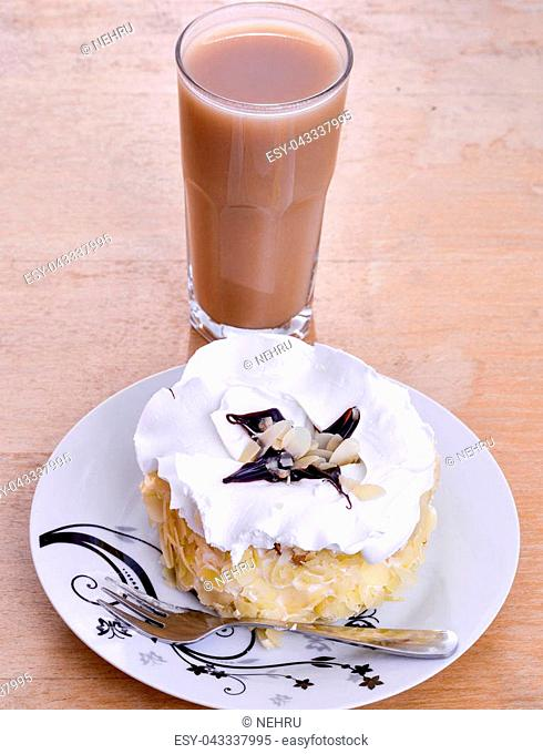 almond cake in a plate on wood background and glass of a boza,image