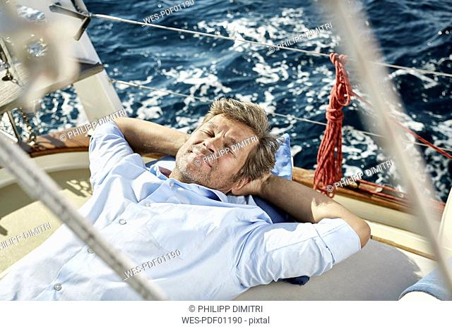 Portrait of smiling mature man lying on deck of his sailing boat