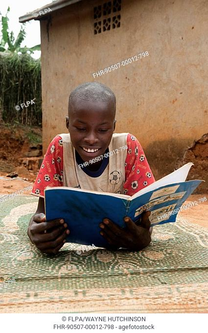 Child reading from educational book at home, Rwanda