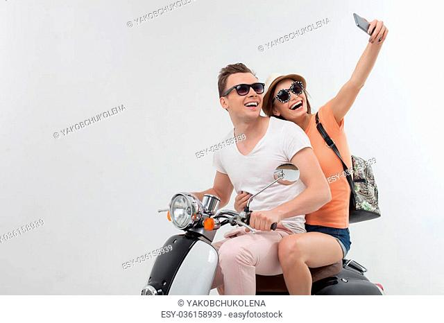 Lets make this moment everlasting. Portrait of cute man and woman traveling by scooter and smiling. They are sitting and making selfie on the mobile phone