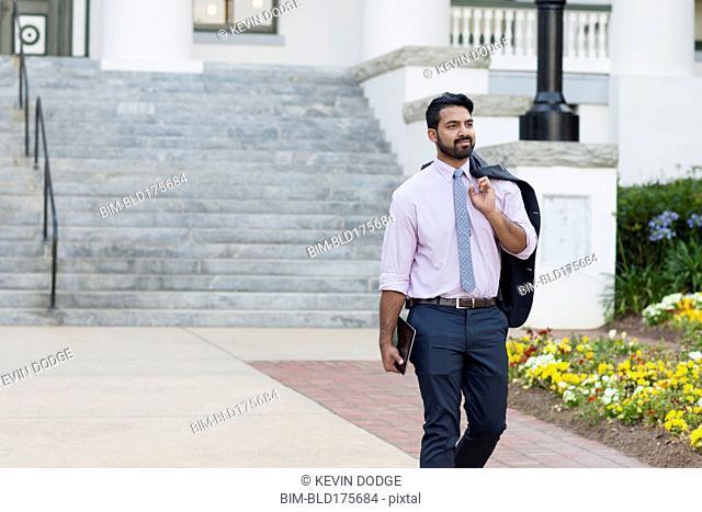 Indian businessman carrying digital tablet on sidewalk