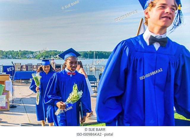 Students in graduation gowns, at graduation ceremony