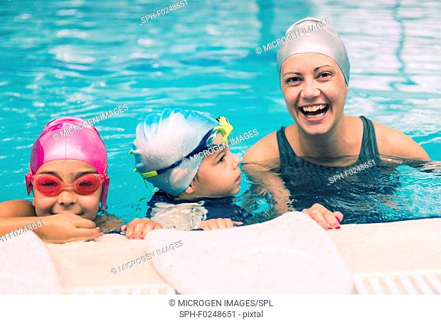 Cheerful swimming instructor having fun with children during swimming lesson