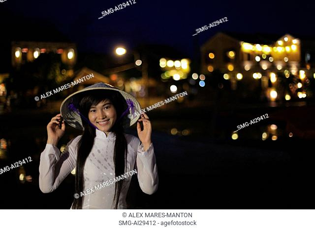 Young woman wearing traditional Vietnamese outfit at night, Vietnam