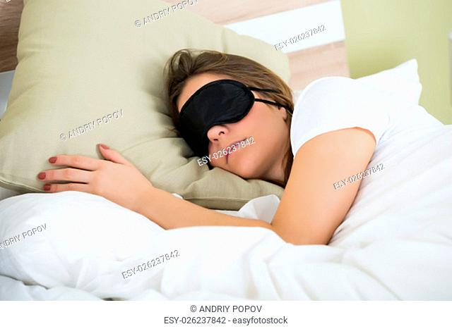 Young Woman Wearing Eye Mask While Sleeping On Bed