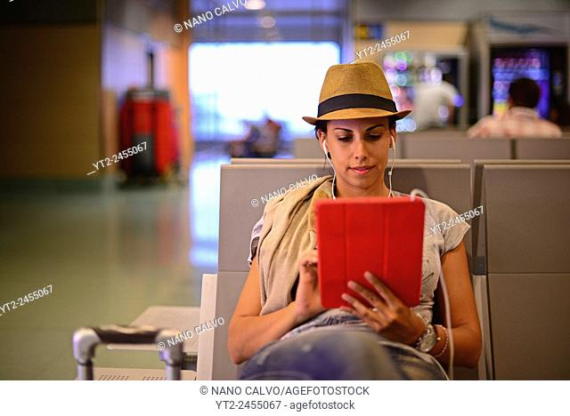 Young woman using tablet in airport