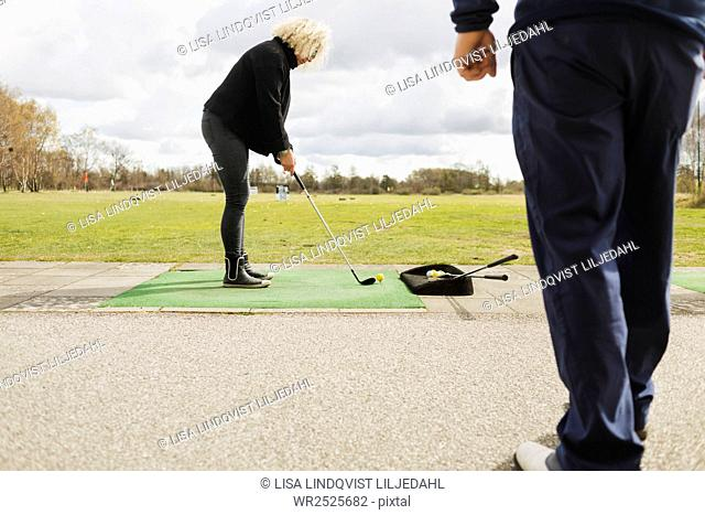 Friends practicing golf at driving range