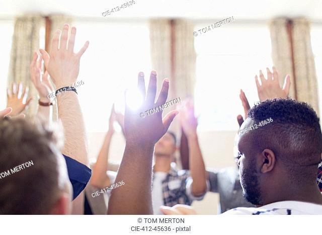 Men praying with arms raised in prayer group