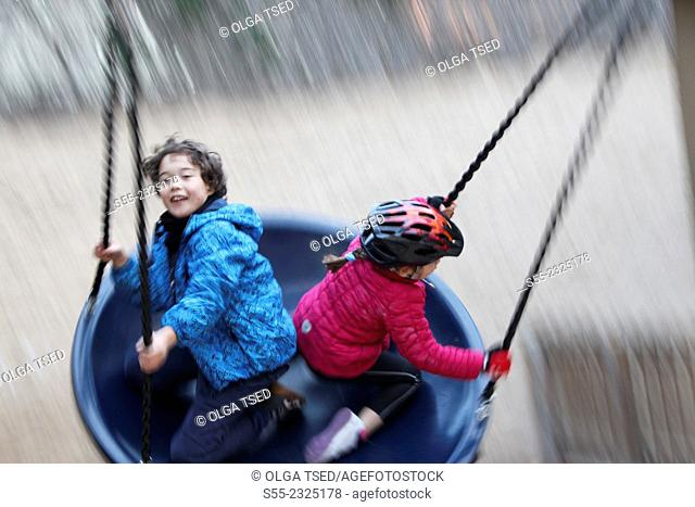 Two kids of 7 and 9 year old swinging. Barcelona, Catalonia, Spain