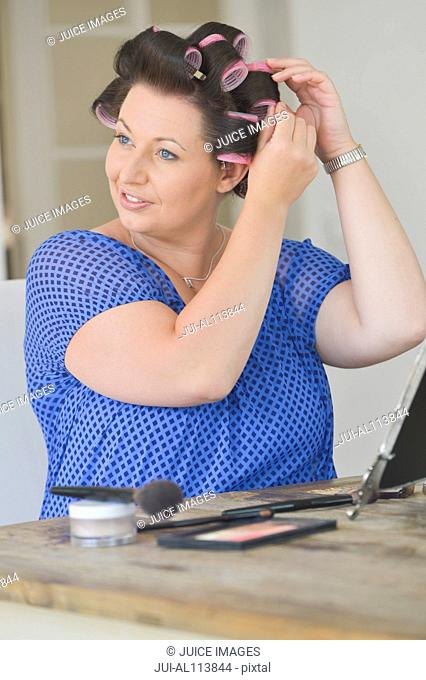 Mid adult woman adjusting hair rollers