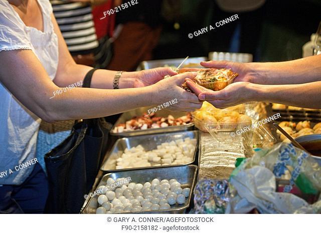 Woman buys okonomiyaki meal at Takadanobaba obon festival in Tokyo, Japan