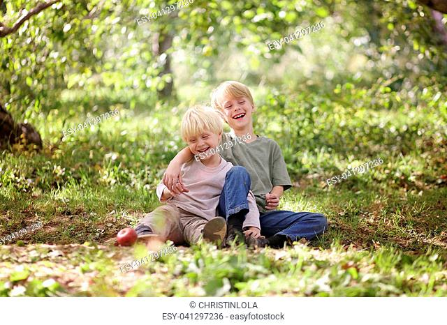 Two happy little boy children, brothers, are sitting in the forest with their arms around each other, laughing
