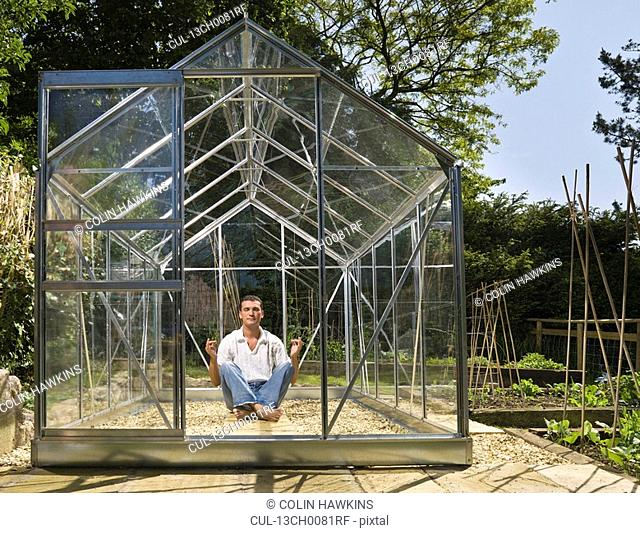 Man meditating in greenhouse in garden