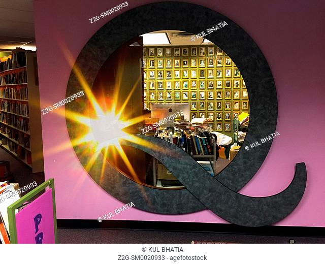 Q for Queer, a round window in a Pride library full of gay literature, art, and other material, Ontario, Canada