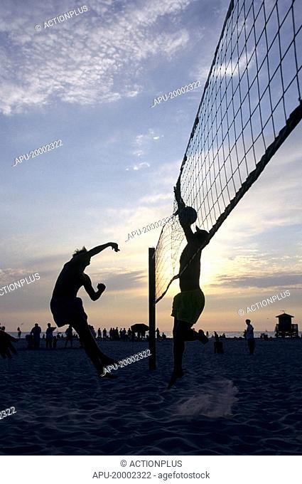 Beach volleyball match at sunset