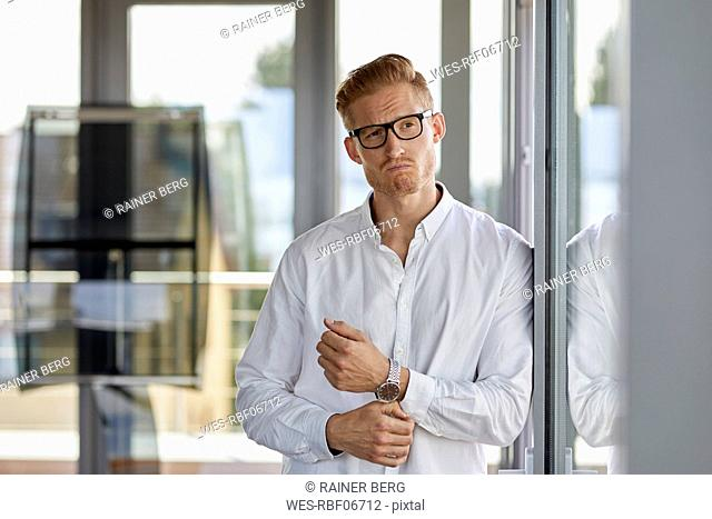 Portrait of grimacing businessman in office leaning against window
