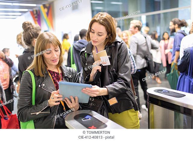 Women with digital tablet at turnstile