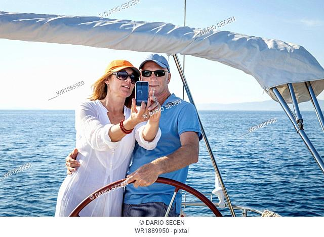 Mature couple sailing together, taking pictures, Adriatic Sea, Croatia