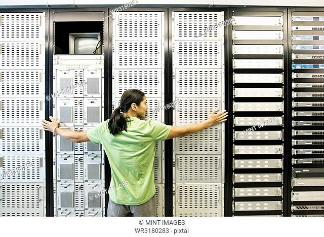 Computer technician working in a large computer server room