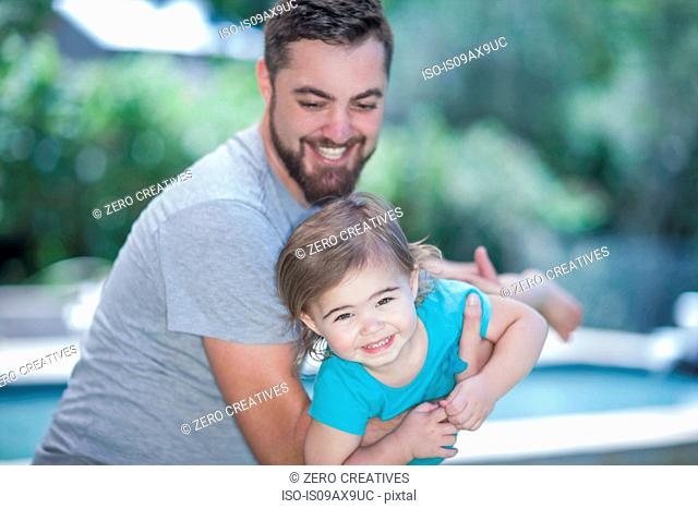 Father swinging daughter by pool