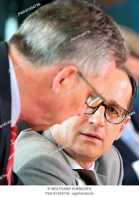 Interior minister Thomas de maiziere (CDU, l) and justice minister Heiko Maas (SPD) talk to each other at the start of the cabinet meeting in Berlin, Germany
