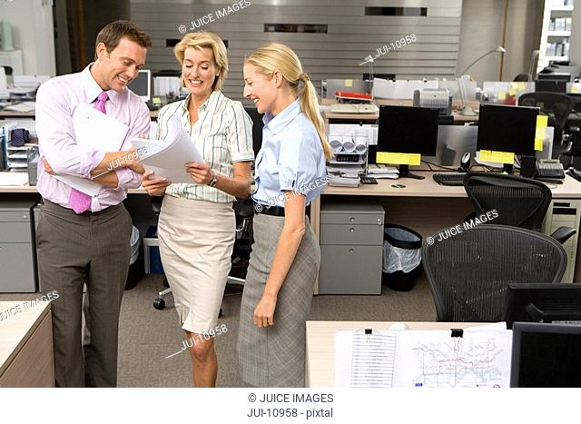 Businesswoman showing paperwork to colleagues in office, smiling, elevated view