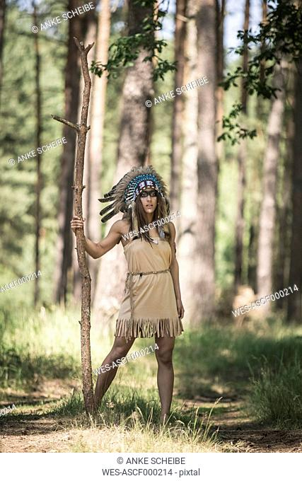 Young woman masquerade as an Indian standing in the woods