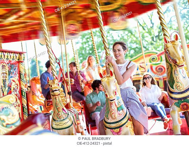 Woman sitting on horse on carousel in amusement park