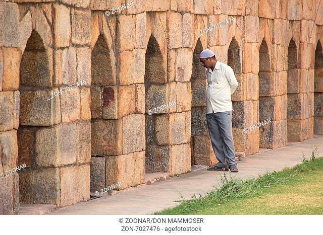 Indian man standing by the wall at Mausoleum of Gh