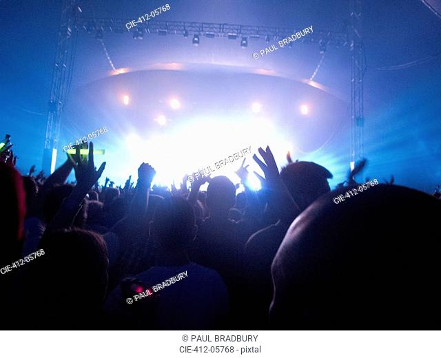 Silhouette of crowd facing stage at music festival