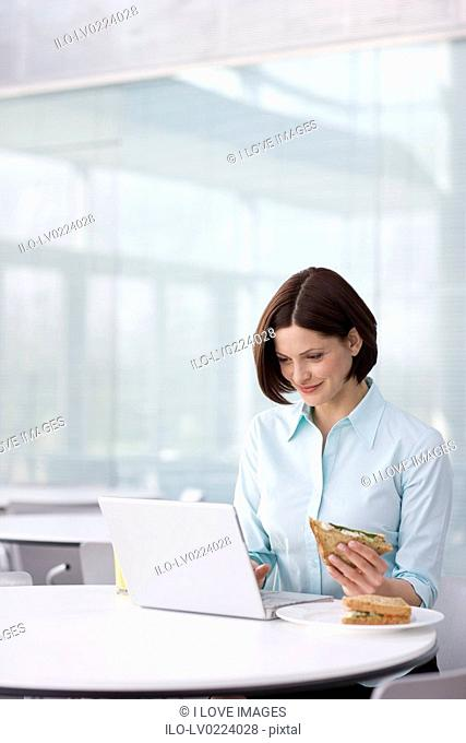 A woman on her lunch break using a laptop computer