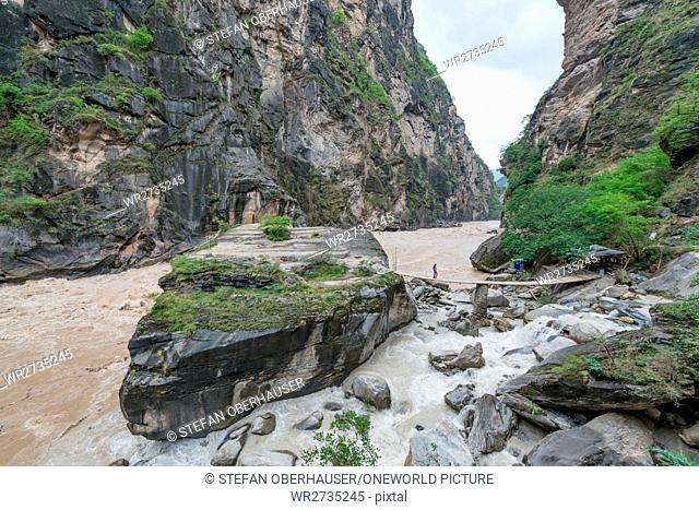 China, Yunnan Sheng, Diqing Zangzuzizhizhou, hike (2-day tour) to the Tigersprung Gorge of the Yangtze River, tourist on the bridge to the rock in the Yangtze...