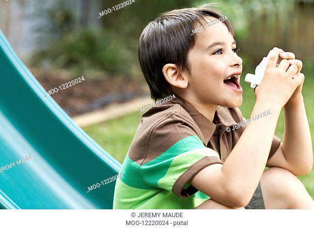 Little boy on slippery slide in park using inhaler