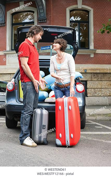 Germany, Leipzig, Couple standing with luggage in front of car